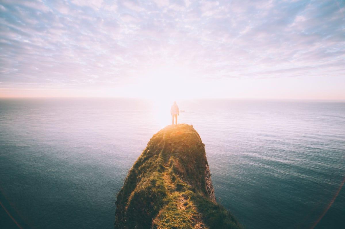 La mer, espace de liberté : un homme sur une corniche face à l'océan au soleil couchant