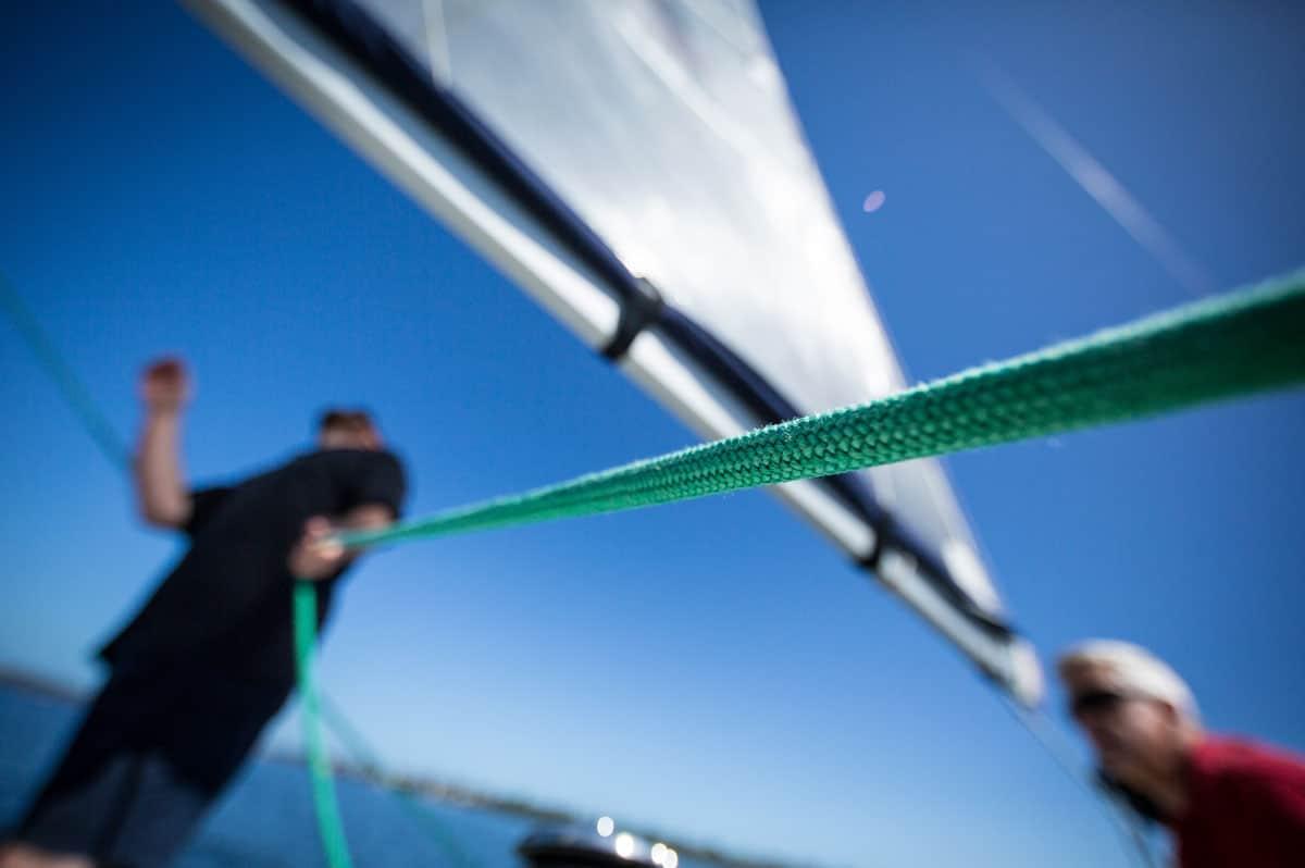 Un homme tire sur un bout pendant une navigation en voilier