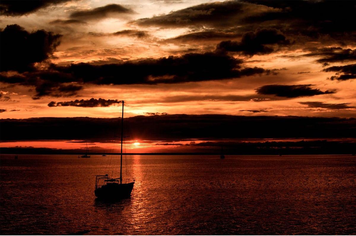 Un voilier mouille dans la pénombre d'un coucher du soleil nuaugeux