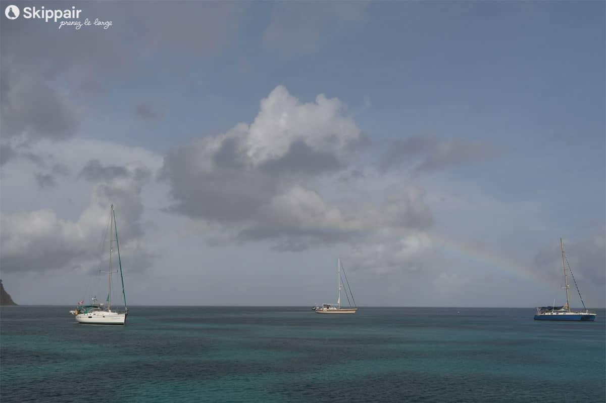 Dans la baie de Chatham, aux Grenadines, des voiliers au mouillage sous un arc-en-ciel